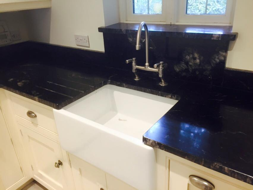 Black and white kitchen counter sink with traditional faucet
