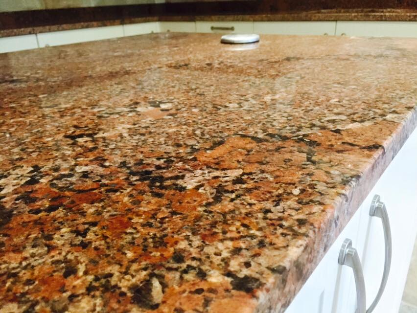 Bronze speckled kitchen island with white cabinets