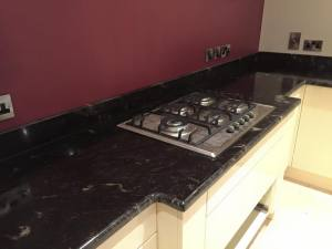 Black granite kitchen surface with rouge wall